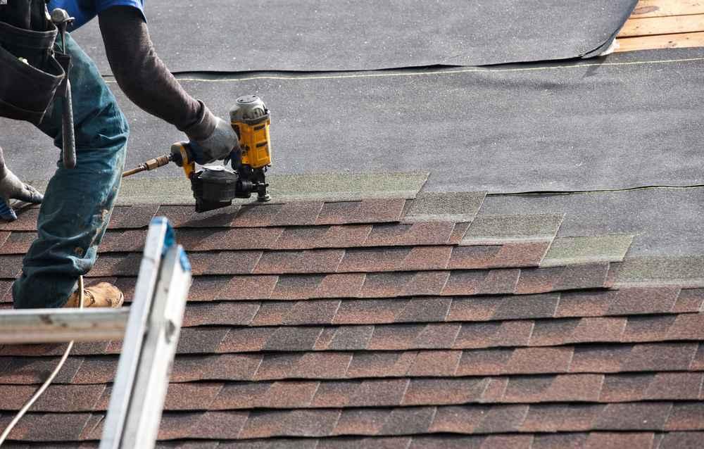 Roofer installing an asphalt shingle roofing system